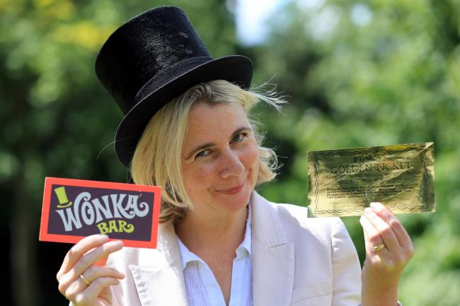 Auctioneer Catherine Southon holds the Golden Ticket and Wonka Bar