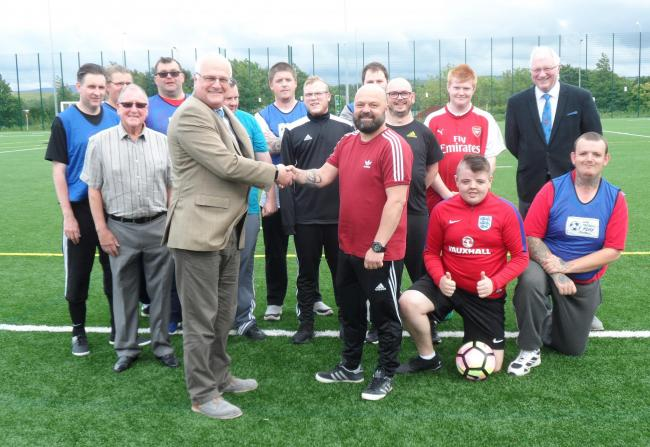 Worshipful Master Garyth Orton and members of Workington's St John's Lodge hand over £250 to West Cumbria United coach Jonathan Ostle and team members