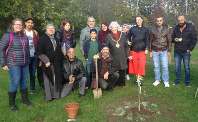 Carlisle's Syrian refugees planting a tree in Bitts Park with the former Mayor of Carlisle