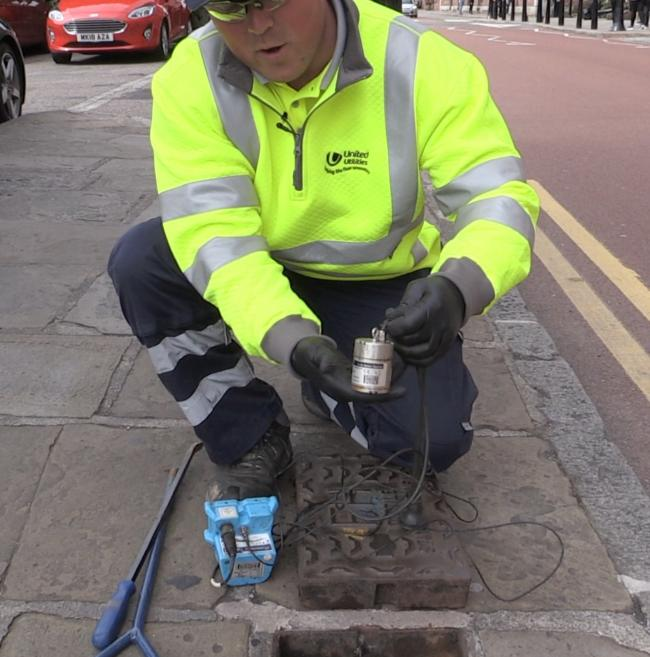 A United Utilities engineer installs a leakage logger