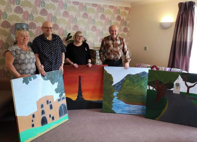 Staff and residents of MHA Amathea in Workington with paintings donated by Lakes College art students