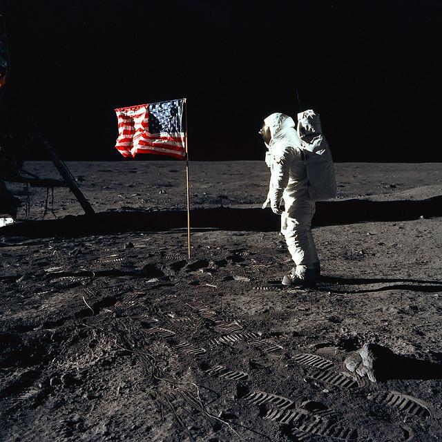 Astronaut Buzz Aldrin, lunar module pilot of the first lunar landing mission, poses for a photograph beside the deployed United States flag during an Apollo 11 Extravehicular Activity (EVA) on the lunar surface. The Lunar Module (LM) is on the left, and t