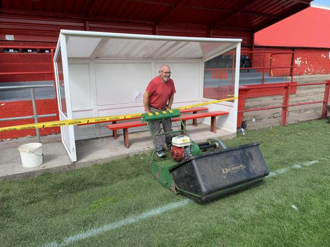 n A volunteer helps out cutting the grass on the Borough Park pitch ready for the new season's start