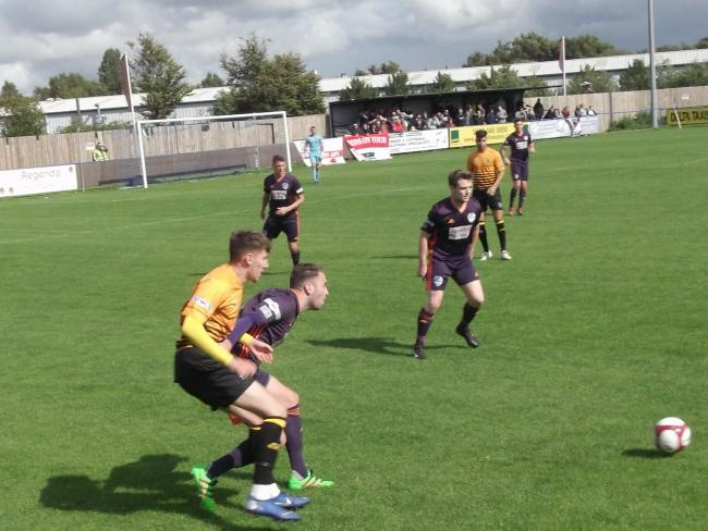 IN THE THICK OF IT: Reds' new signing Matty Clarke, yellow, tussles with home defender Luke Denson 