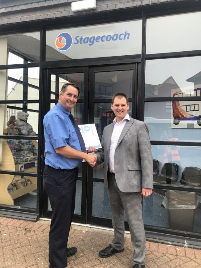 The image shows Stagecoach Cumbria and North Lancashire MD Mark Whitelocks (on the right) with Carlisle driver Darren Johnson who was Star of the Month in June.