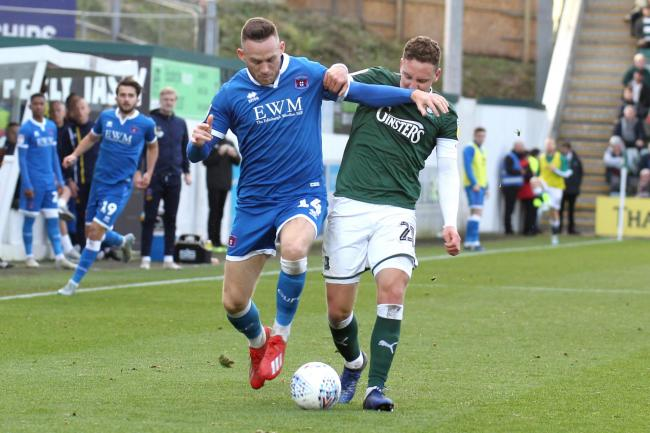 Tussle: Defender Gethin Jones battles with Plymouth's Callum McFadzean for the ball in Carlisle United's 2-0 loss at Home Park on Saturday (Photo: Barbara Abbott)