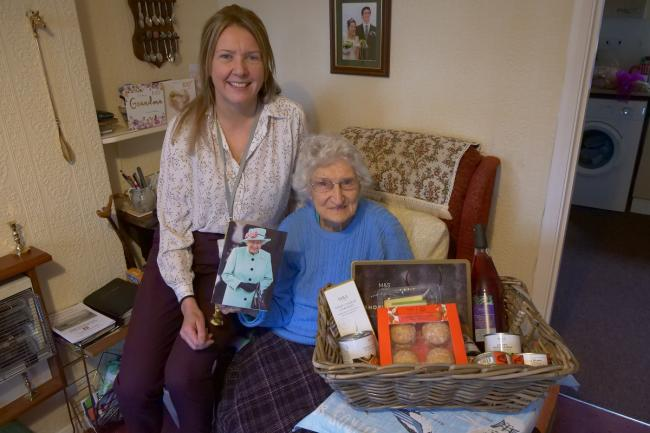 CCHA's Pamela Armstrong presents 100-year-old resident, Noreen Thwaites, with a birthday hamper and flowers