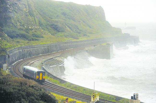 Weather. A Northern Rail train makes its way slowly along the coast as waves crash in at Parton near Whitehaven. Picture: STUART WALKER
