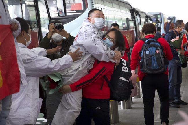 A medical worker from China's Jilin Province, in red, embraces a colleague from Wuhan as she prepares to return home at Wuhan Tianhe International Airport in Wuhan in central China's Hubei Province, Wednesday, April 8, 2020. Within hours of China