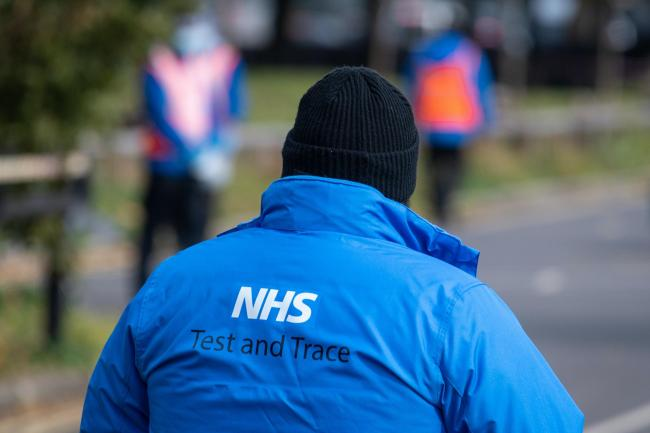 An NHS Test and Trace logo on a member of staff's jacket (Dominic Lipinski/PA)