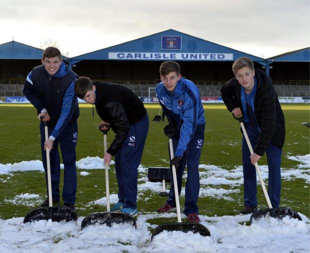 News and Star: Carl Taylor, second right, with fellow youth team players clearing snow from the Brunton Park pitch in the 2015/16 season