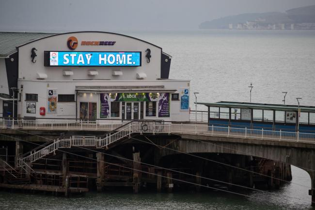 A 'Stay Home' sign is displayed on Bournemouth pier in Dorset