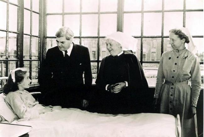 Creator of the NHS Aneurin Bevan (second left) talks to its first patient, 13-year-old Sylvia Diggory,