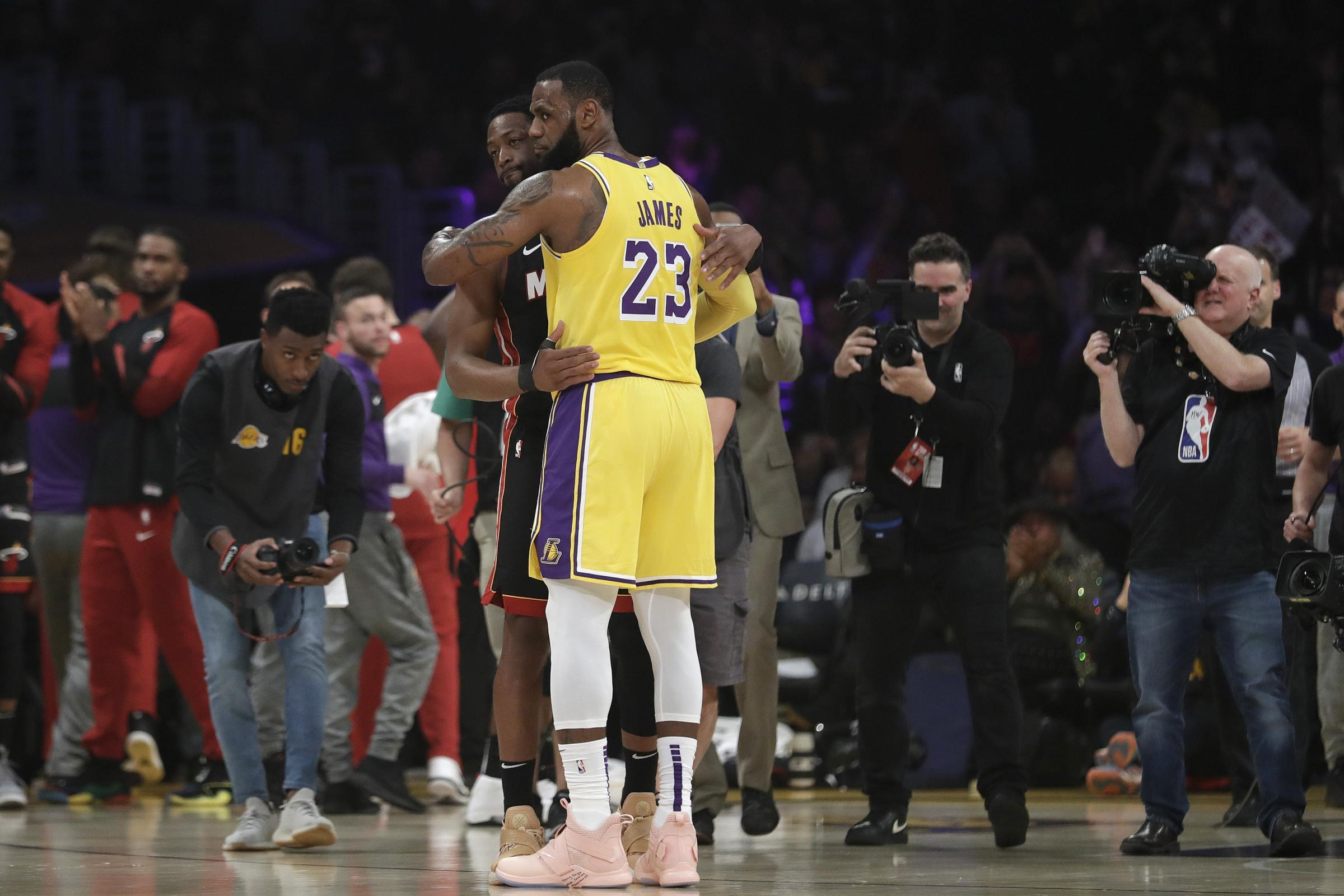 Los Angeles Lakers forward LeBron James hugs ex teammate and current Miami Heat player Dwyane Wade
