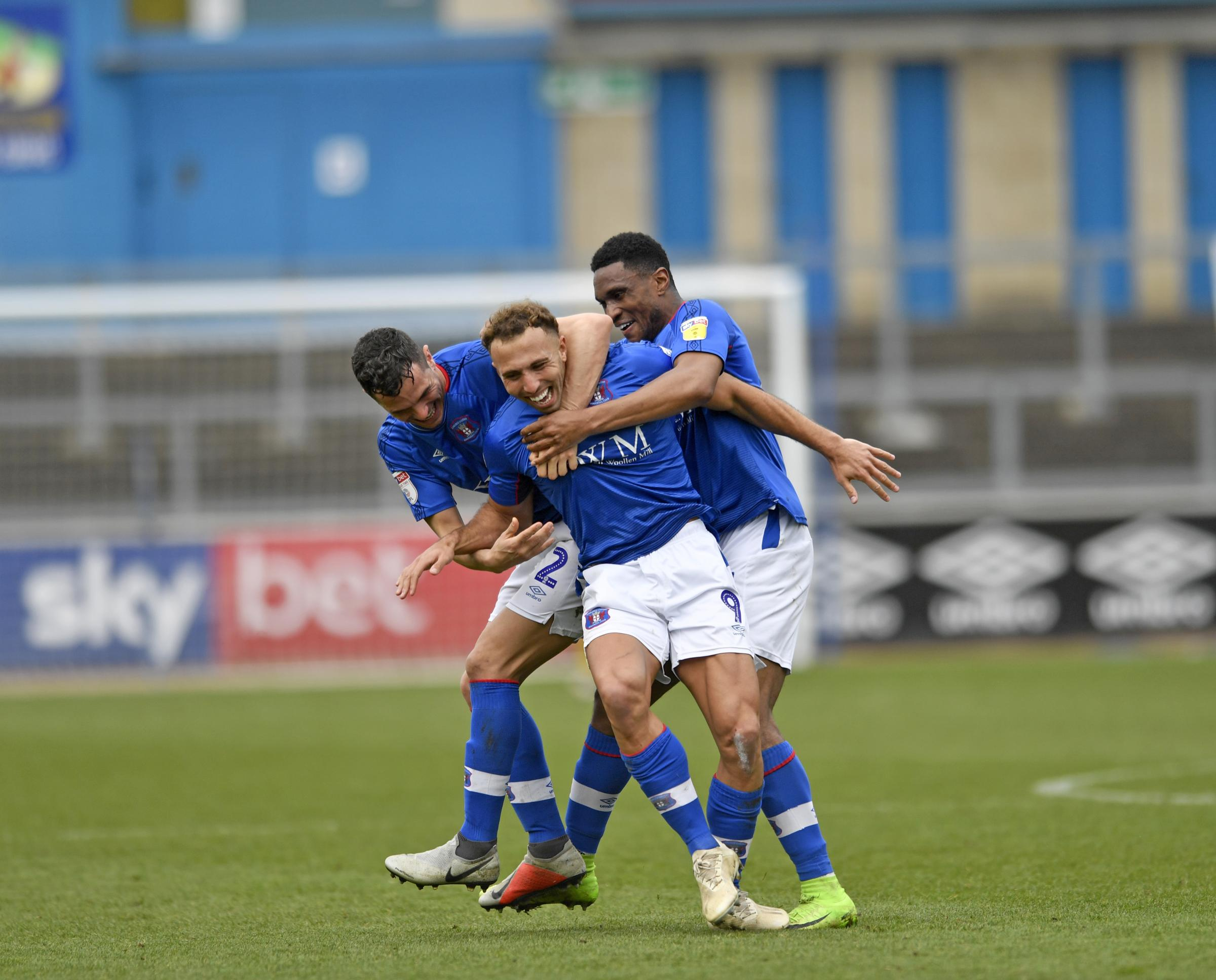 Winner: Hallam Hope is mobbed by team-mates Gary Miller and Kelvin Etuhu after scoring Carlisle United's winner in their 3-2 success against Bury (Photo: Stuart Walker)