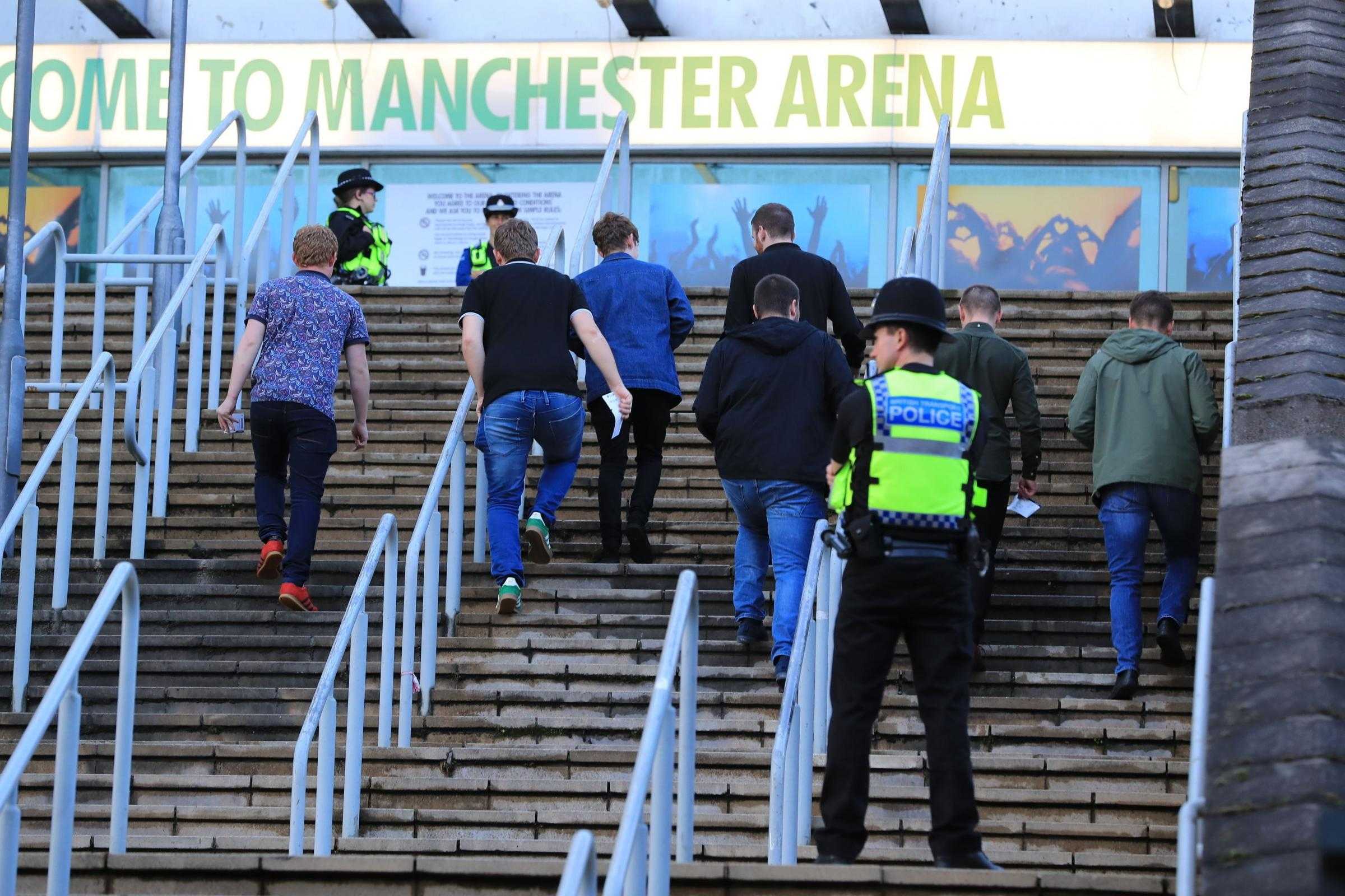 People arrive at the Manchester Arena under police watch