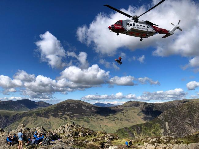 Safe at last: A lady walker is winched from the Cumbrian fells by a Coasguard helicopter